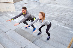 Couple doing squats on city street stairs royalty free stock photos