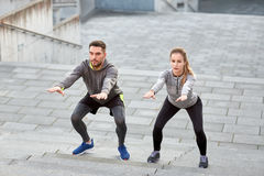 Couple doing squats and exercising outdoors Royalty Free Stock Image