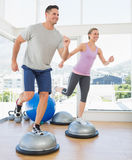 Couple doing step aerobics in fitness studio Royalty Free Stock Images