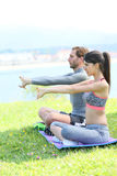 Couple doing stretching excercises by the sea Royalty Free Stock Image