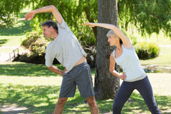 Couple doing stretching exercise Stock Photos