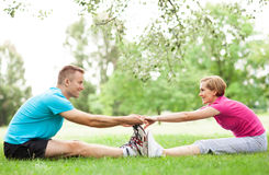 Couple doing stretching exercises in park Stock Image