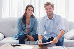 Couple doing their accounts sat in a couch Royalty Free Stock Image