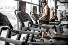 Couple doing treadmill run. Young adult men and women doing running exercise on treadmill in modern fitness center. Toned image Royalty Free Stock Images