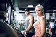 Couple doing treadmill run. Young adult men and women doing running exercise on treadmill in modern fitness center. Toned image Royalty Free Stock Image