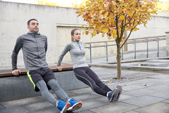 Couple doing triceps dip on city street bench Royalty Free Stock Images