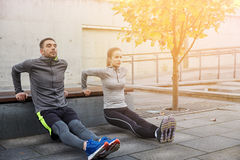Couple doing triceps dip on city street bench Stock Image