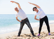 Couple doing yoga on the beach stock photography