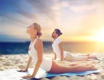 Couple doing yoga and cobra pose on beach Stock Photos