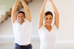 Couple doing yoga exercise. Portrait of lovely couple doing yoga exercise at home Royalty Free Stock Photos