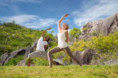 Couple doing yoga exercises on beach Royalty Free Stock Photos