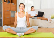 Couple doing yoga with laptop. Smiling girl doing yoga at home while men browsing internet . Focus on girl Royalty Free Stock Photos