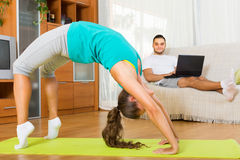 Couple doing yoga with laptop. Smiling men browsing internet while girl doing yoga indoor. Focus on girl Royalty Free Stock Images