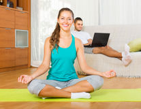 Couple doing yoga with laptop. Young guy browsing internet while girl doing yoga at home. Focus on girl Royalty Free Stock Photography