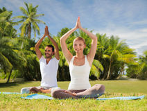 Couple doing yoga in lotus pose outdoors Stock Photo