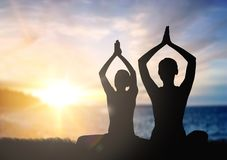 Couple doing yoga in lotus pose over sunset royalty free stock photos
