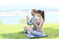 Couple doing yoga meditation by the seaside Royalty Free Stock Photography