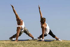 Couple doing yoga in nature. Beautiful blue skies in bacground Stock Photos