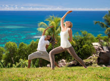 Couple doing yoga over natural background and sea Stock Photos