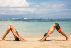 Couple doing yoga and relaxation exercises by the sea Stock Photos