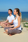 Couple doing yoga by the sea Royalty Free Stock Photos