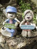 Couple Doll pottery with Happy Smile. Happy boy and girl doll pottery with 2 Thai word : Boy : Have a healthy rich, Girl : be rich Royalty Free Stock Image