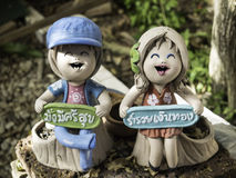 Couple doll pottery with wish well words. Happy boy and girl doll pottery with 2 Thai word : Boy : Have a healthy rich, Girl : be rich Royalty Free Stock Images