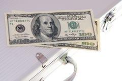 Couple dollar banknotes on aluminum suitcase. Couple on hundred dollar banknotes and aluminum suitcase isolated on white Stock Photo
