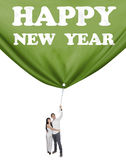 Couple drag a banner new year in studio Royalty Free Stock Photo