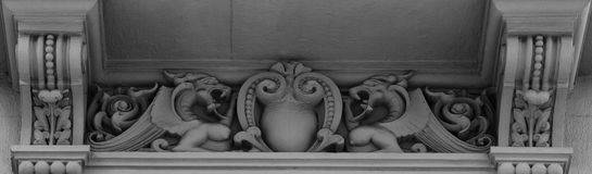 A couple of dragons facing each other. Shot in black and white, detail on the sculpture on the facade of this historic building representing some characters / Royalty Free Stock Images