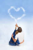 Couple drawing heart in the sky Stock Photos
