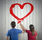 Couple drawing a heart. Young couple drawing a big red heart Stock Images