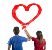 Couple drawing a heart. Young couple drawing a big red heart Stock Image