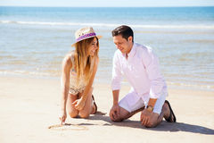 Couple drawing initials on the sand. Cute girlfriend drawing a heart and her initials and her boyfriend's on the sand during their vacation at the beach Royalty Free Stock Photo