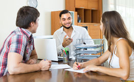 Couple drawing up an agreement at office Stock Photos