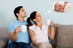 Couple Dreaming Of Having Child Together At Home. Happy Couple Dreaming Of Having Child Together While Sitting On Sofa At Home Royalty Free Stock Photo