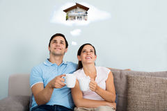 Couple Dreaming Of Having Future Home. Happy Couple Dreaming Of Having Future Home While Sitting On Sofa Stock Image