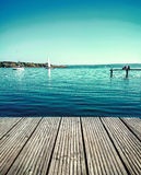 Couple dreaming on water jetty by lake Stock Photo