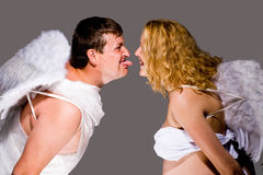 Couple dressed as angels. Making funny faces at one another Royalty Free Stock Images