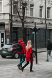 Couple dressed in bright red walking in city stock images
