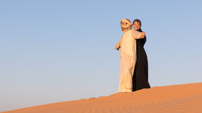 Couple dressed in traditional arab clothing in desert. Couple dressed in traditional arab clothing in desert at sunrise Royalty Free Stock Image