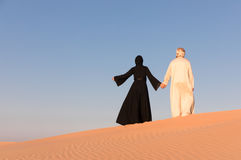 Couple dressed in traditional arab clothing in desert. Couple dressed in traditional arab clothing in desert at sunrise Royalty Free Stock Photography