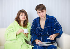 Couple in dressing gowns watching TV Stock Photography