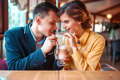 Couple drink a cocktail together from the straws. Happy couple drink a cocktail together from the straws, restaurant on background. Man and women at romantic stock photo