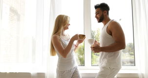Couple drink coffee morning near window mix race man woman smile stock video