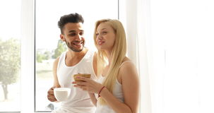 Couple drink coffee morning sitting near window mix race man woman smile stock video
