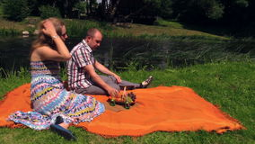 Couple drink, eat bun cinnamon on plaid stream. Summer picnic. Couple drink lemonade and eat fresh bun with cinnamon on plaid in nature near stream. Picnic for stock footage