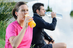 Couple Drinking. Young athletes sitting and drinking water and isotonic drink for recovering from trainning Royalty Free Stock Images