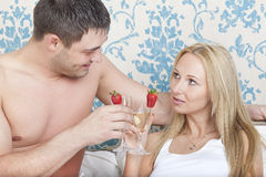 Couple drinking in bed Stock Images