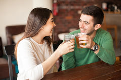Couple drinking beer at a bar Stock Images